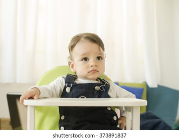 Portrait of a cute toddler. Beautiful baby boy sitting in a high chair waiting, looking away.