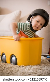 Portrait of cute toddler boy in black helmet sitting in the toy box. Playing at home