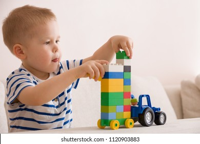 Portrait of cute toddler boy playing with colorful plastic toy bricks at the table at home.