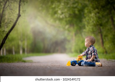 Portrait of cute toddler boy sitting on the ground and playing with toy tractor and sand in the park. Child walking outdoors. Lifestyle.