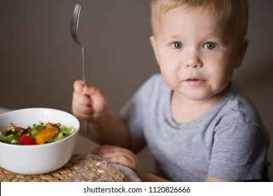 Portrait of cute toddler boy sitting at the table at home and eating.