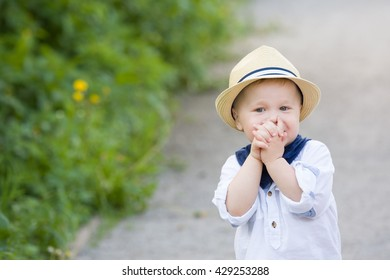 Portrait of a cute toddler boy in straw hat walking in the park on a sunny summer day. Adorable child walking in the park. Outdoors. Childhood and lifestyle concept