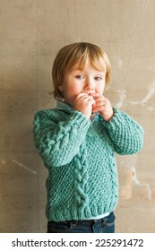 Portrait of a cute toddler boy, wearing green knitted pullover