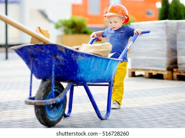 Portrait of cute toddler builder in hardhats with wheelbarrow working outdoors. Little boy's dream concept