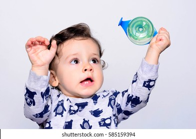 Portrait of a cute toddler drinking water from the bottle. One year old kid lifting up the baby cup. Adorable curly hair boy being thirsty.