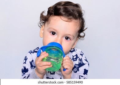 Portrait of a cute toddler drinking water from the bottle. One year old kid holding the baby cup. Adorable curly hair boy being thirsty.