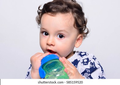 Portrait of a cute toddler drinking water from the bottle. One year old kid playing with the baby cup. Adorable curly hair boy being thirsty.
