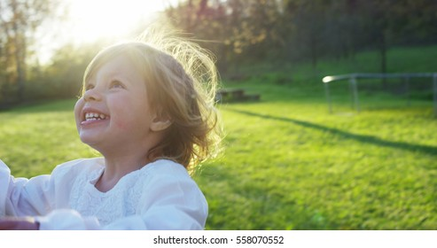 A portrait of cute toddler little two years old girl running happy on green widow in a woods. Concept of love for nature, protection of kids,innocence, fun, joy, carefree childhood, freedom