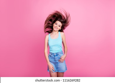 Portrait of cute trendy cheerful excited attractive beautiful slim skinny dressed in blue t-shirt and denim skirt woman, hair is flying in wind, isolated on pink background