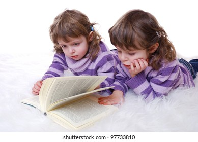 portrait of cute twin girls reading a book