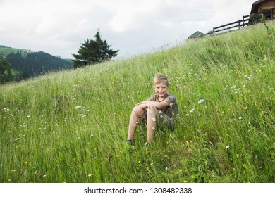 Portrait of cute white blond boy sitting at grassy hill at scenic countryside on summer day. Boy smiling and looking at camera. Happy summer holidays and vacations concept. Horizontal color photgraphy