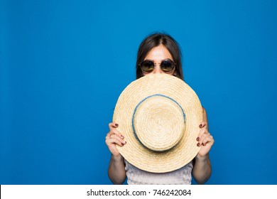 Portrait of cute woman covering face with round hat on blue