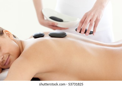 Portrait of a cute woman having a massage with stones at the spa