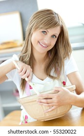 Portrait of a cute woman showing a cake in the kitchen at home