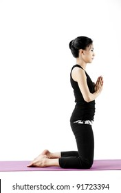Portrait of a cute young asian female practicing yoga on a mat