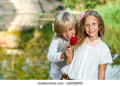 Portrait of cute young boy giving red rose to girl at lakeside.