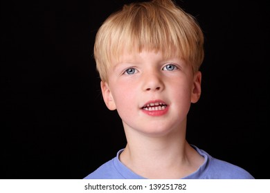 Portrait of a cute young boy on black background