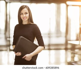 Portrait of cute young business woman smiling in the office, the hands of the folder