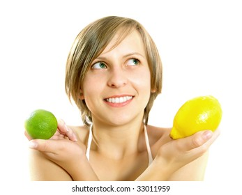 Portrait of a cute young Caucasian blond lady with a nice colorful striped summer dress who is smiling and she is holding a fresh lemon and a lime in her crossed hands. Isolated on white.