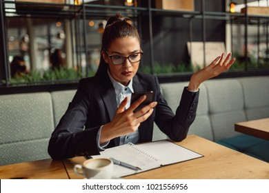 Portrait of cute young confused business woman using smartphone and looking at the screen.