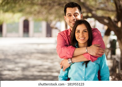 Portrait of a cute young couple hugging and smiling outdoors