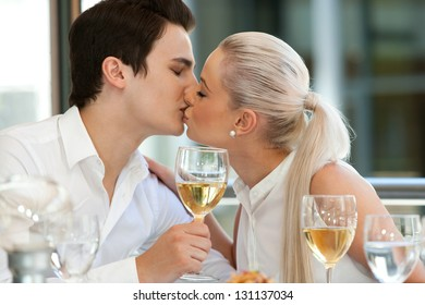 Portrait of cute young couple kissing at dinner table.