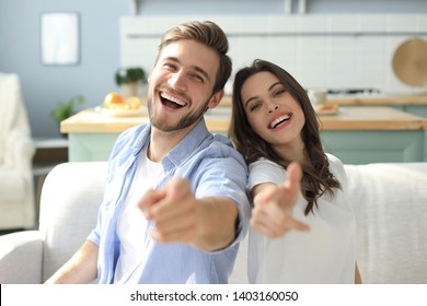 Portrait of cute young couple pointing and laughing, sitting in sofa.