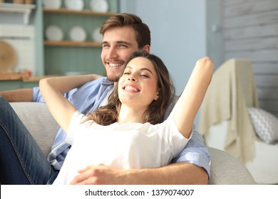Portrait of cute young couple sitting in sofa.