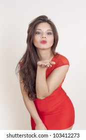 Portrait of a cute young female blowing a kiss at you against white background