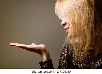 Portrait of a cute young female blowing a kiss towards copyspace.