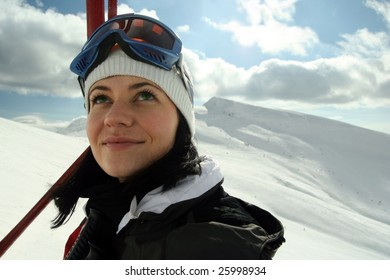 Portrait of cute young female in chair lift ,after skiing, looking at sky.
