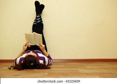 Portrait of a cute young female laying by the wall reading a book