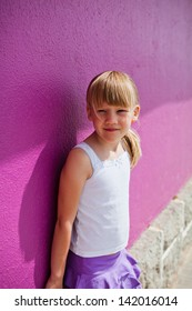 Portrait of cute young girl against purple painted concrete wall