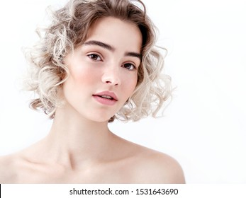 Portrait of a cute young girl with bare shoulders, clean fresh skin and cute curls. Charming caucasian model with natural make-up on white background. Natural feminine beauty. Soft daylight.