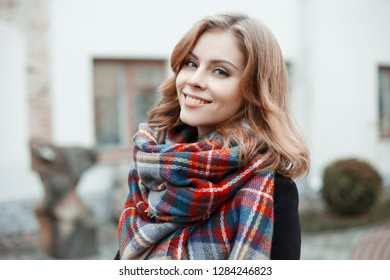 Portrait of a cute young girl with beautiful blue eyes with an attractive smile with curly blond hair in winter stylish clothes on the background of a modern building. Charming girl