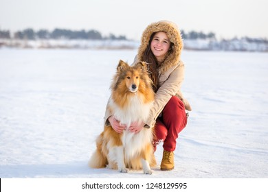 Portrait of cute young girl with collie dog on snowy landscape, copyspace