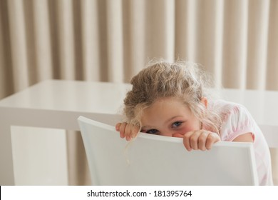 Portrait of a cute young girl hiding face behind chair in the house