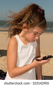 Portrait of a cute young girl playing with smart phone on the beach. Modern lifestyle, modern generation concept.