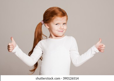 Portrait of a cute young girl showing thumbs up.