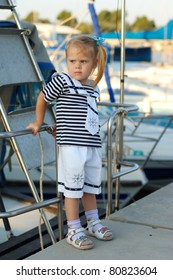 Portrait of cute young girl in yacht harbor in sailor suit