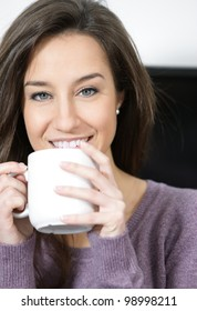 Portrait of a cute young lady with a cup of coffee
