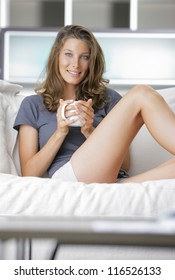 Portrait of a cute young lady sitting on sofa with a cup of coffee