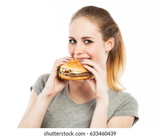 Portrait of a cute young woman biting into a burger, isolated on white