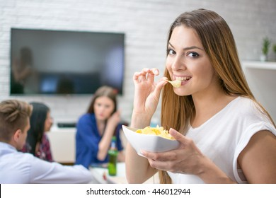 Portrait of cute young woman eating potato chips while sitting with her friends at home.