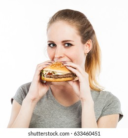 Portrait of a cute young woman eating a burger, isolated on white