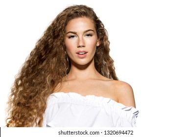 Portrait of cute young woman with luxury long curly hair and natural make-up. Pretty model wearing nice white top posing in studio and looking at camera with temptation. Isolated on white