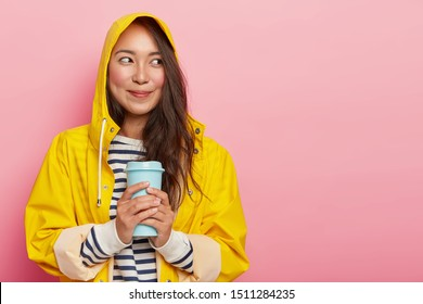 Portrait of cute young woman wears raincoat, warms with hot beverage, looks happily aside, has dimples on rouge cheeks, enjoys rainy weather in comfortable streetwear, isolated on pink wall.