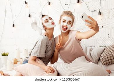 肖像可爱的年轻女性发送亲吻甜蜜微笑,制作有趣的面孔图片。 开朗可爱的朋友采取自拍照在家里面部化妆品面膜。 护肤概念