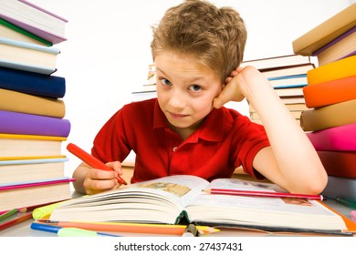 Portrait of cute youngster sitting among stacks of literature and making notes in textbook with red highlighter