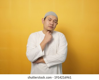 Portrait of cynical Asian muslim man with suspicious expression looking and starring, mistrust misdoubt concept
